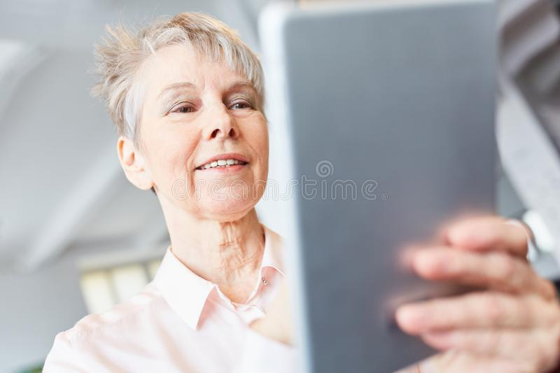 Senior woman with tablet. Computer reads message online stock image