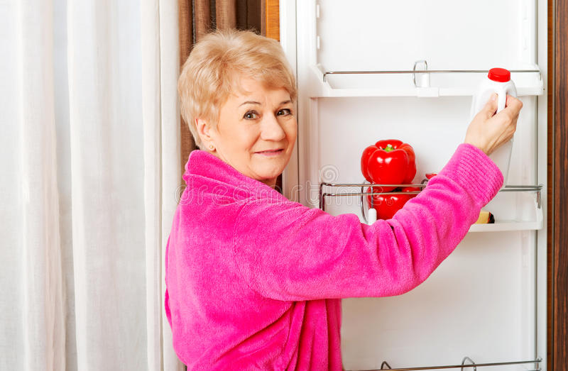 Senior woman taking a bottle of milk from fridge royalty free stock image