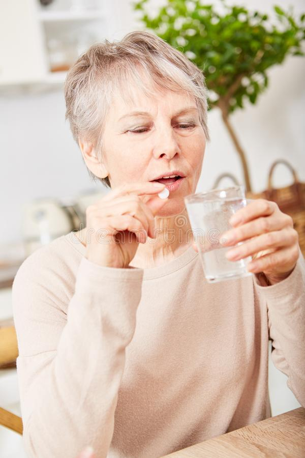 Senior woman taking medicament. Tablets at home stock photography