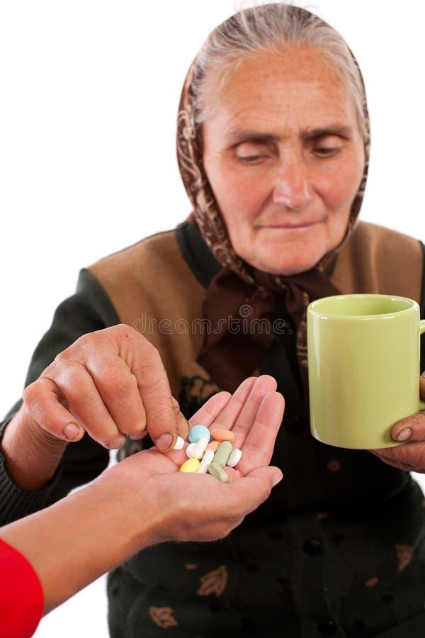 Download Senior woman taking pills stock photo. Image of pills - 16146118