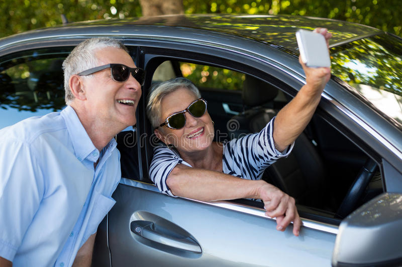 Senior woman taking selfie with man stock photos