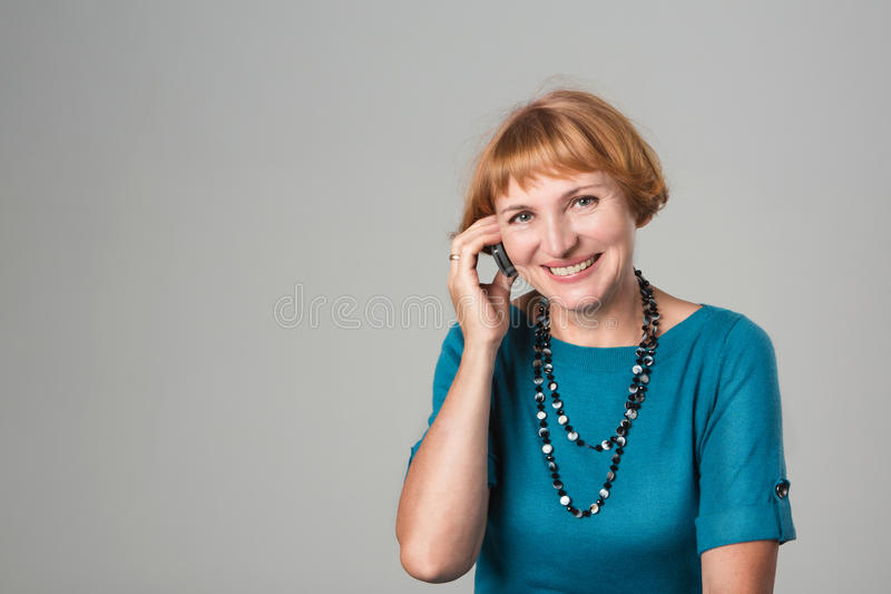Senior Woman Talking On Mobile Phone. Closeup portrait of happy woman using a phone. Studio shot stock image