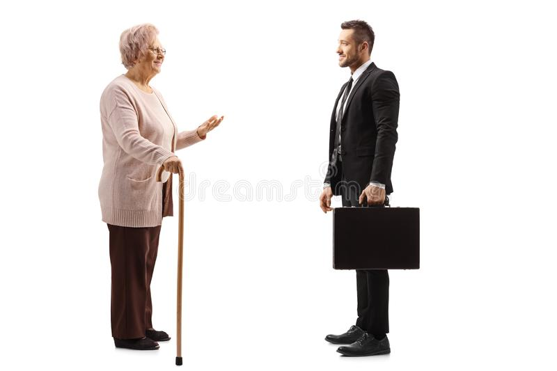 Senior woman talking to a businessman with a suitcase. Full length profile shot of a senior women talking to a businessman with a suitcase isolated on white stock photo