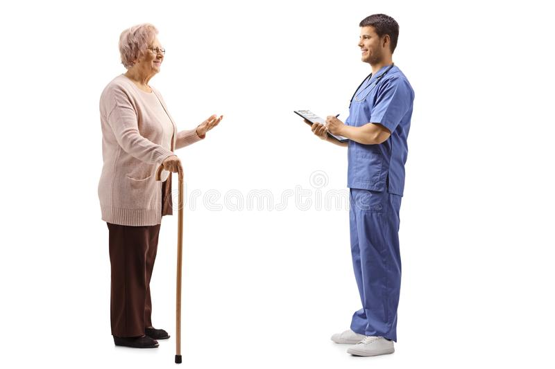 Senior woman talking to a young male doctor in a blue uniform. Full length profile shot of a senior women talking to a young male doctor in a blue uniform stock photography