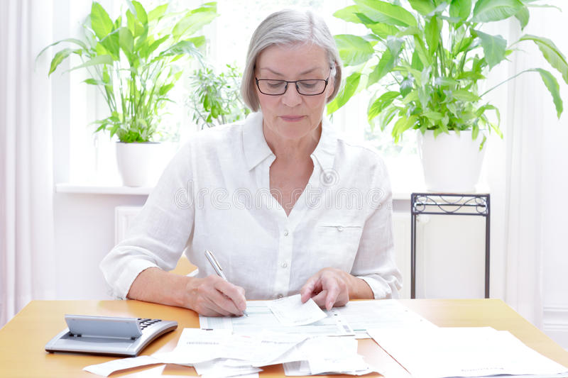 Senior woman tax declaration forms. Senior german woman at home with a calculator and lots of bills and receipts, filling out the printed forms of the annual tax royalty free stock image