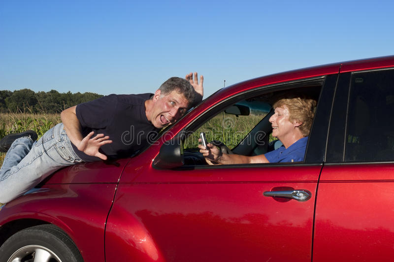 Senior Woman Texting While Driving Car Accident. Humorous look at a serious subject: Texting and using a while driving. A senior mature woman is busy texting on stock photo