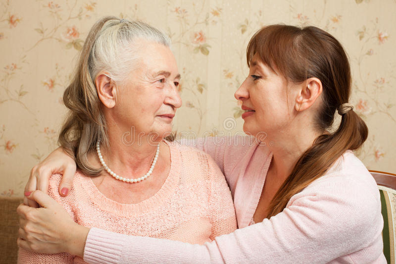 Senior woman with their caregiver at home. Happy family. Portrait of elderly women and adult daughter happily looking at camera. Senior women with their stock images