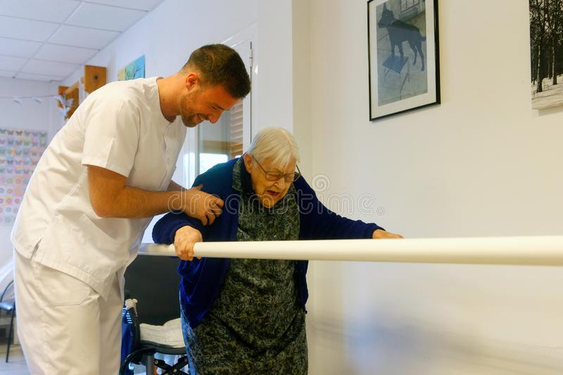 Senior woman during therapeutical activities on a nursing home in Mallorca. Seniors with the help of a male nurse practice some coordination exercise on the gym stock photos