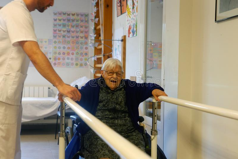 Senior woman during therapeutical activities on a nursing home in Mallorca wide. Seniors with the help of a male nurse practice some coordination exercise on the stock image