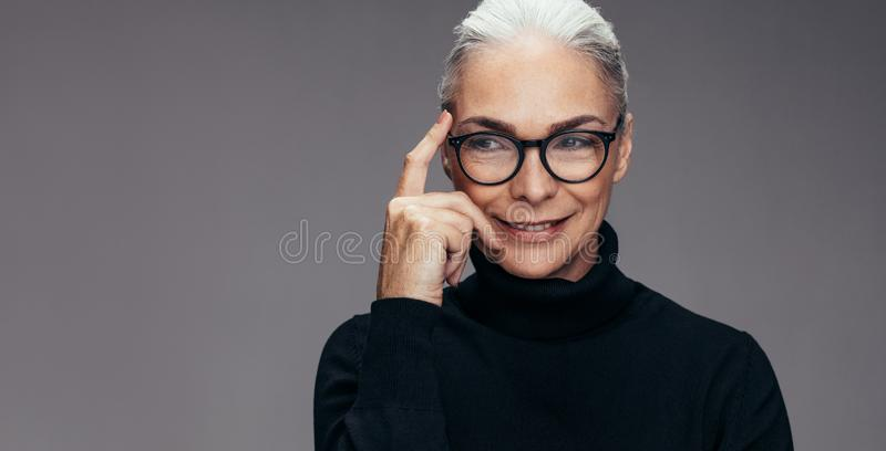 Senior woman thinking of an idea. Close up of a senior woman with eyeglasses looking away and thinking against grey background. Mature woman thinking of an idea royalty free stock photos