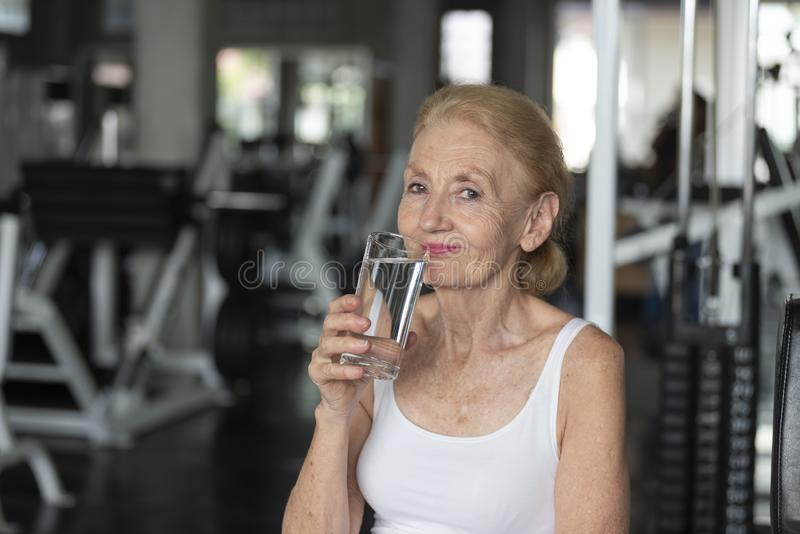 Senior woman thirsty drinking water after exercise in fitness gym. elderly healthy lifestyle royalty free stock photo