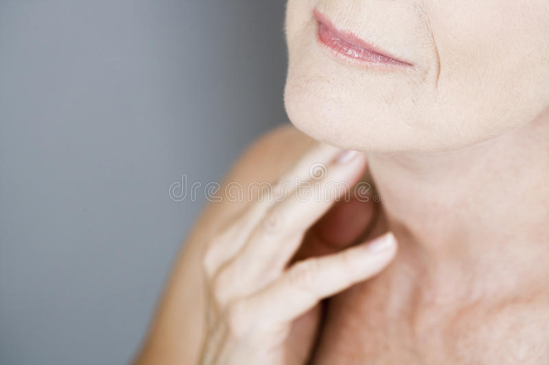 A senior woman touching her neck stock image