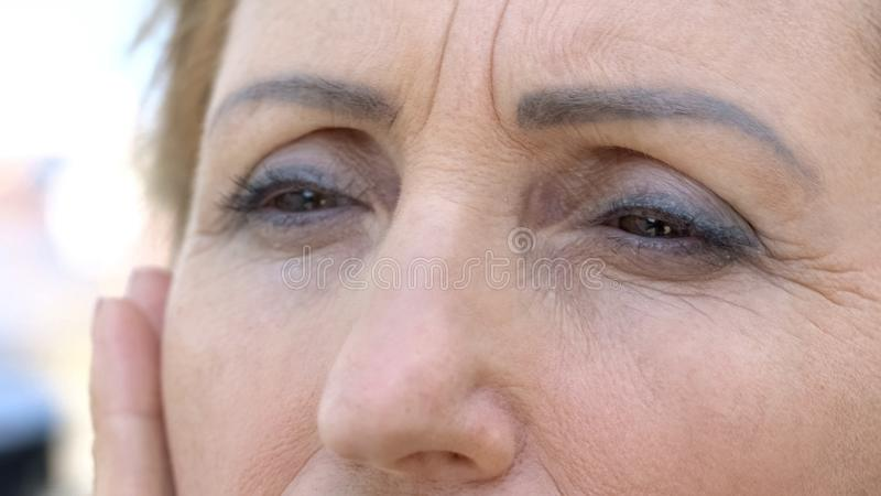 Senior woman touching her wrinkled face, skin aging process, desire to be young royalty free stock photography