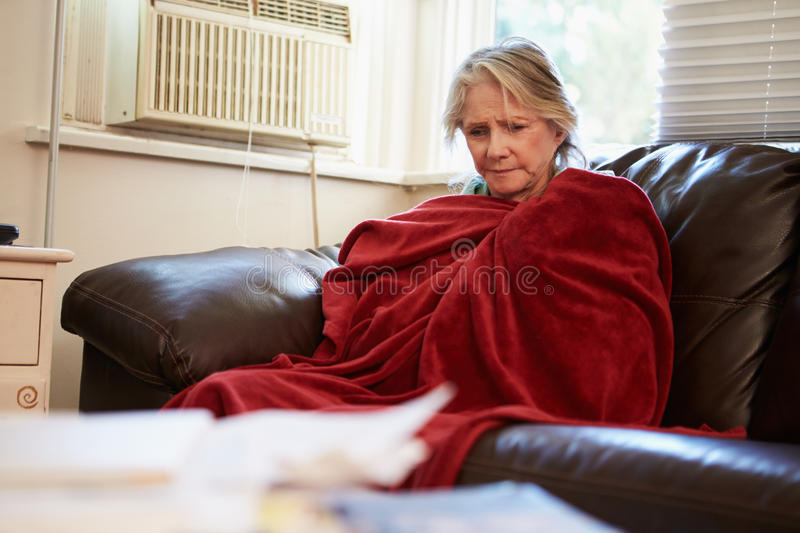 Senior Woman Trying To Keep Warm Under Blanket At Home stock photography