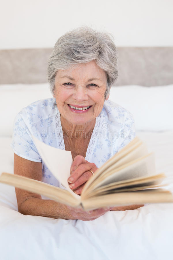 Senior woman turning story book pages. Portrait of happy senior woman turning story book pages in bed at home royalty free stock photos