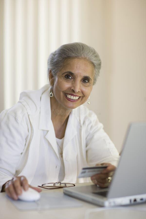 Senior woman using credit card and computer royalty free stock image
