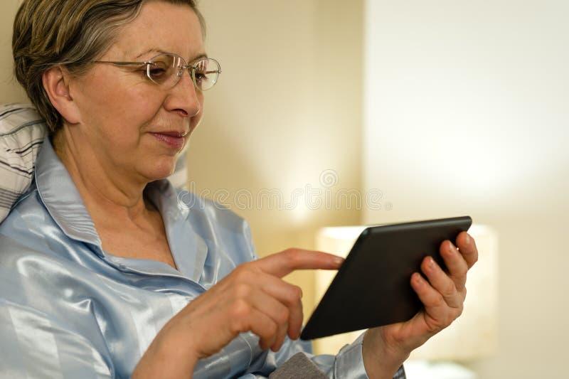 Download Senior Woman Using Digital Tablet In Bed Stock Photo - Image of bedroom, ebook: 30865230
