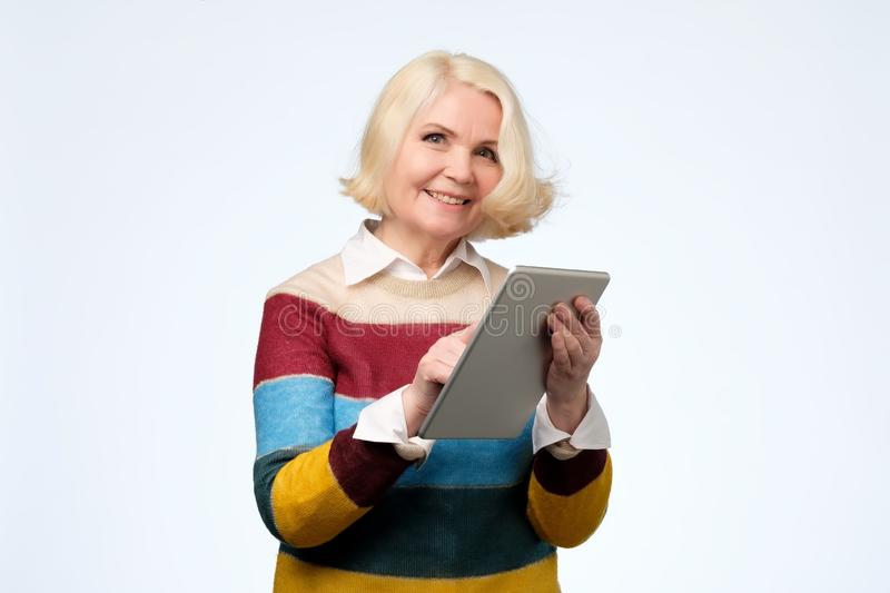 Senior woman using digital tablet surfing web media chatting online, smiling. stock photography