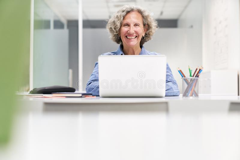 Senior Woman Using Laptop Computer In Co-Working Space stock images