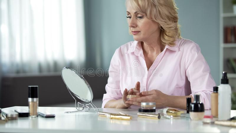 Senior woman using lot of expensive makeup hiding age-related skin changes. Stock photo royalty free stock image
