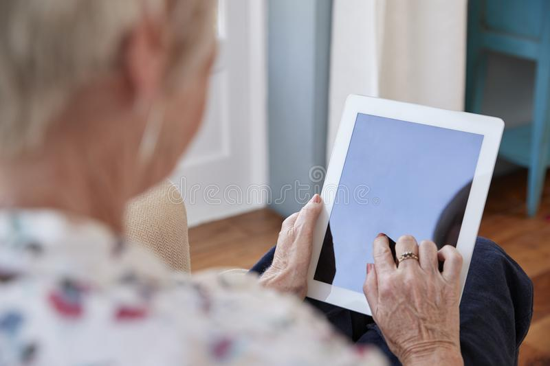 Senior woman using tablet computer, over shoulder view royalty free stock photography