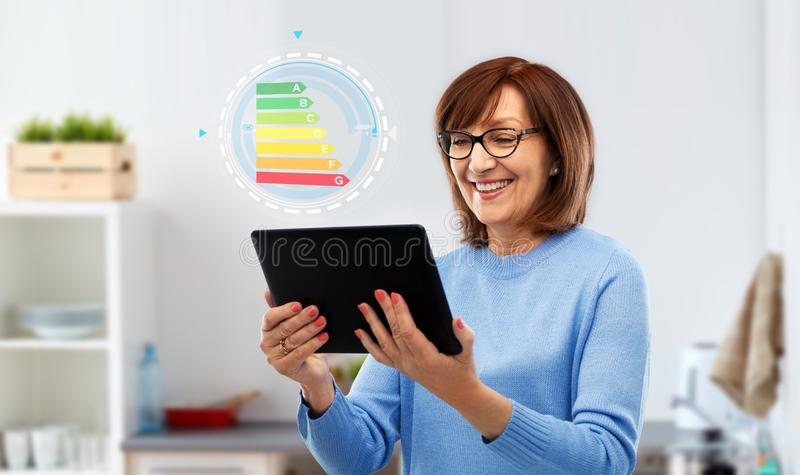 Senior woman using tablet pc with energy chart stock photography