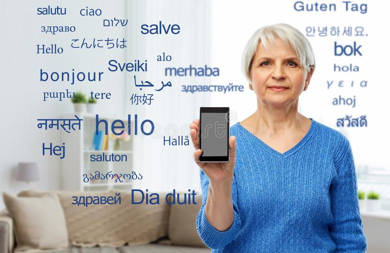 Senior woman using translator on smartphone. Technology, online translator and old people concept - senior woman showing smartphone over greeting words in stock photography