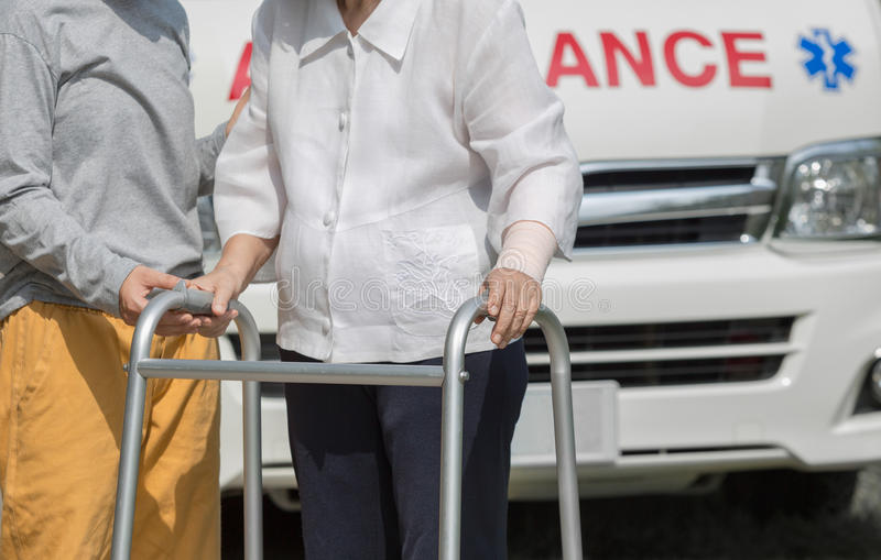 Senior woman using a walker with caregiver. To take ambulance royalty free stock photography