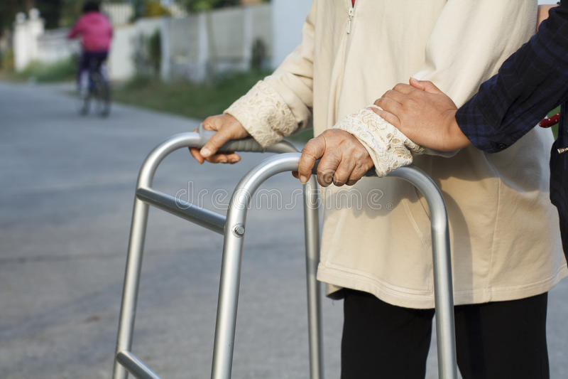 Senior woman using a walker cross street stock image