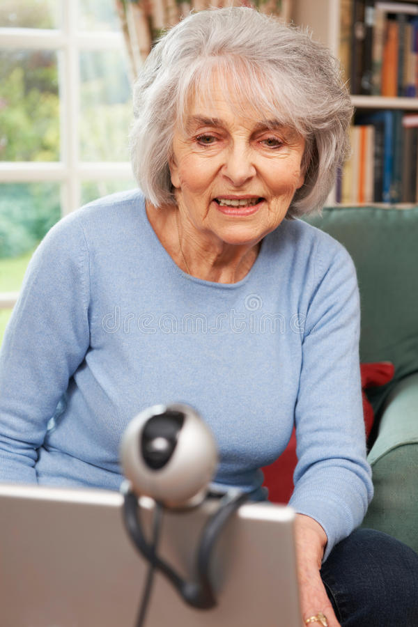Senior Woman Using Webcam To Talk With Family stock photo