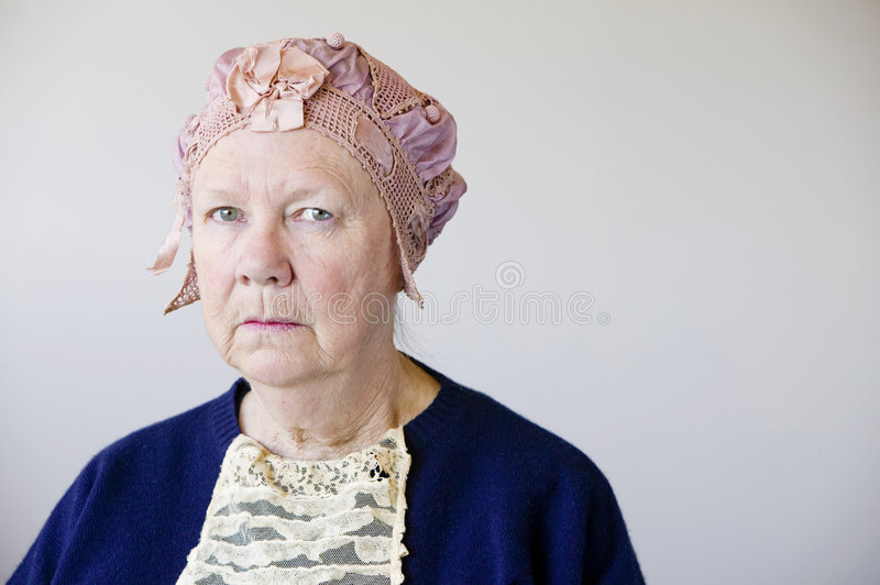 Senior woman with a vintage hat. Dour senior woman in the studio wearing a vintage hat and lace royalty free stock image