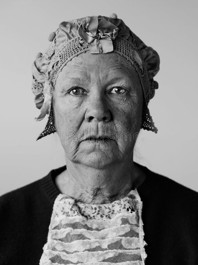 Senior woman with a vintage hat. Dour senior woman in the studio wearing a vintage hat and lace stock photos