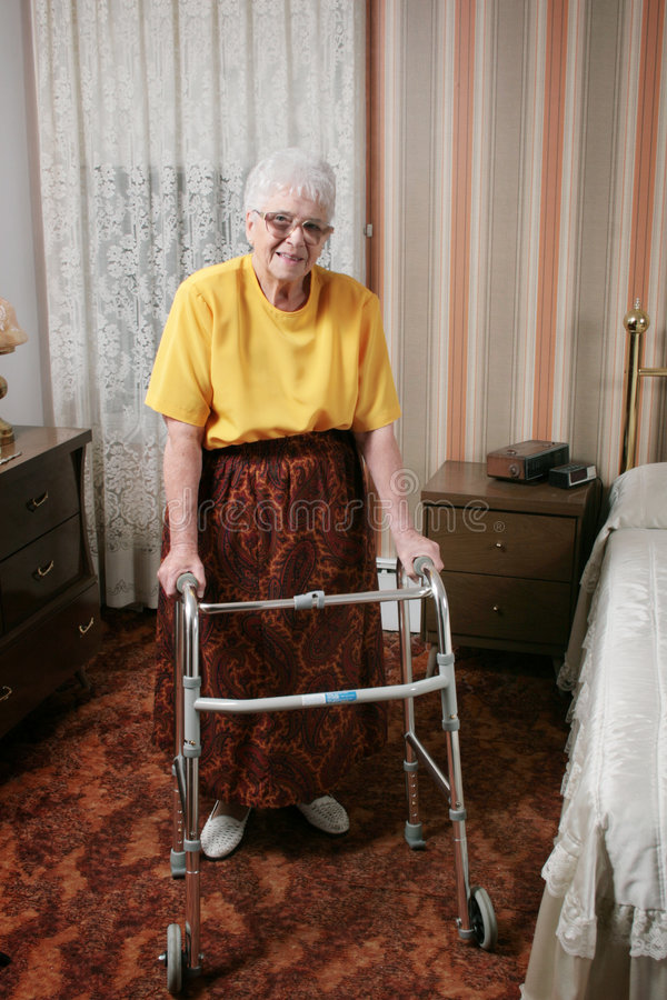 Senior woman and walker. Smiling senior citizen standing with a walker in front of her, in an interior bedroom stock photography