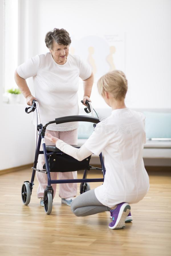 Senior woman with walker trying to walk again and helpful physiotherapist supporting her royalty free stock images
