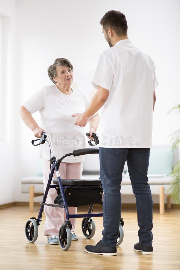 Senior woman with walker and young physiotherapist during session stock photo