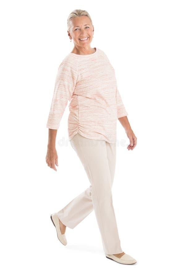 Senior Woman Walking Against White Background royalty free stock image