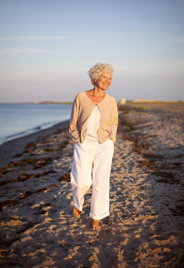 Senior woman walking on the beach stock photos
