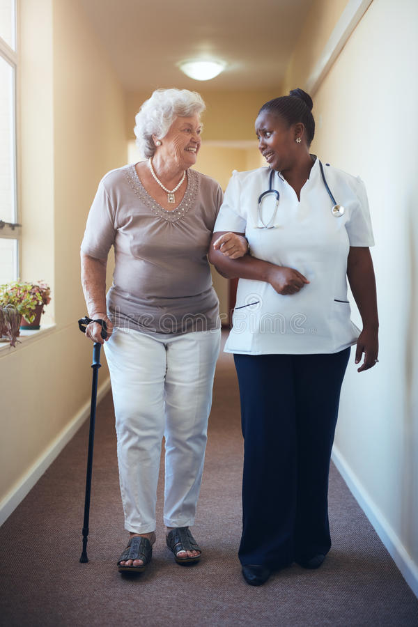 Senior woman walking being helped by female nurse royalty free stock photo