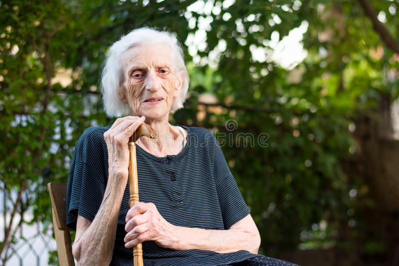Senior woman with a walking cane. Senior woman sitting with a walking cane outdoors stock photography