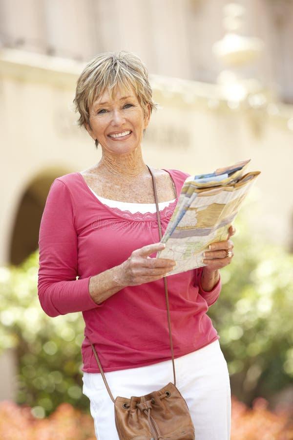Senior Woman Walking Through City Street With Map royalty free stock photos