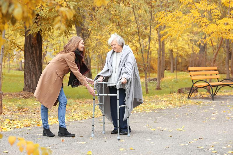 Senior woman with walking frame and young caregiver. Senior women with walking frame and young caregiver in park stock photo