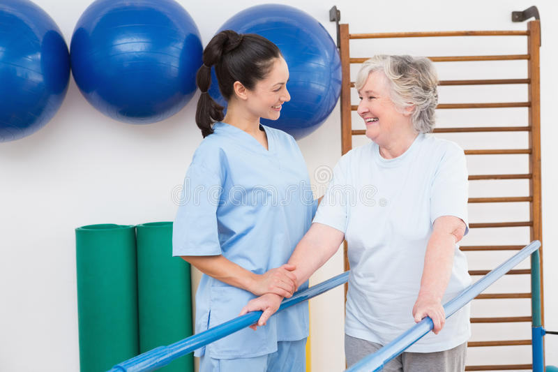 Senior woman walking with parallel bars with therapist. Senior women walking with parallel bars with therapist in fitness studio royalty free stock photos