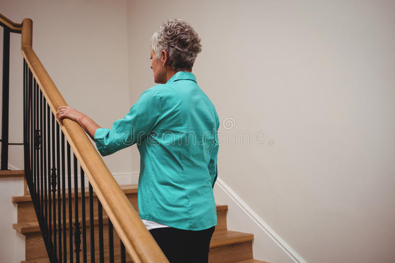 Senior woman walking up stairs royalty free stock image