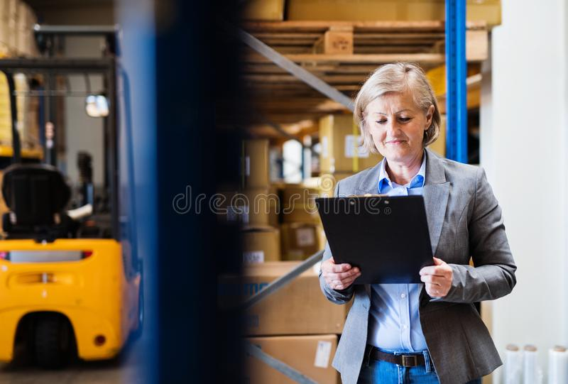 Senior woman warehouse manager or supervisor with clipboard. stock photos