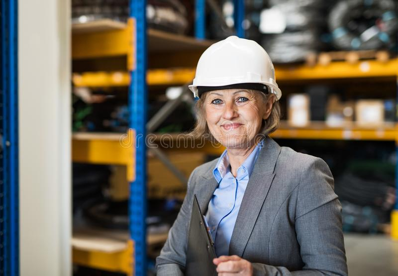 Senior woman warehouse manager or supervisor with white helmet and clipboard. royalty free stock photography