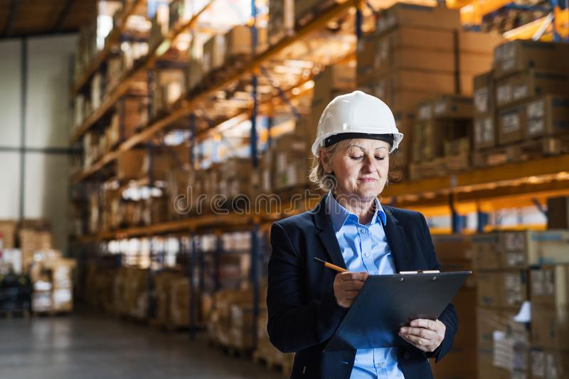 Senior woman warehouse manager or supervisor with white helmet and clipboard. Senior woman warehouse manager or supervisor with a white helmet and clipboard stock photography