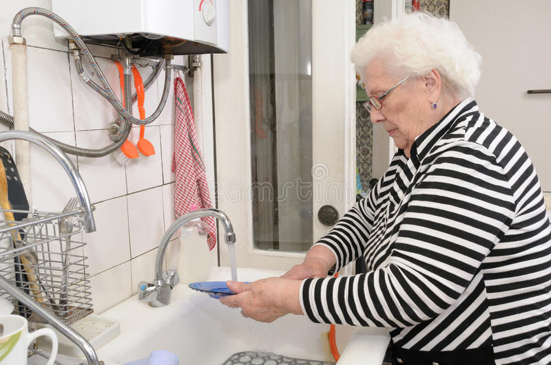 Senior woman washes dishes royalty free stock photography