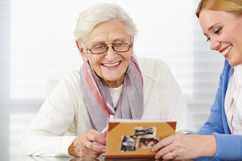 Senior woman watching photo album. Happy senior women watching photo album with eldercare nurse stock images