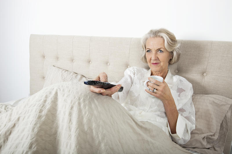 Download Senior Woman Watching TV While Having Coffee In Bed Stock Image - Image: 35914959