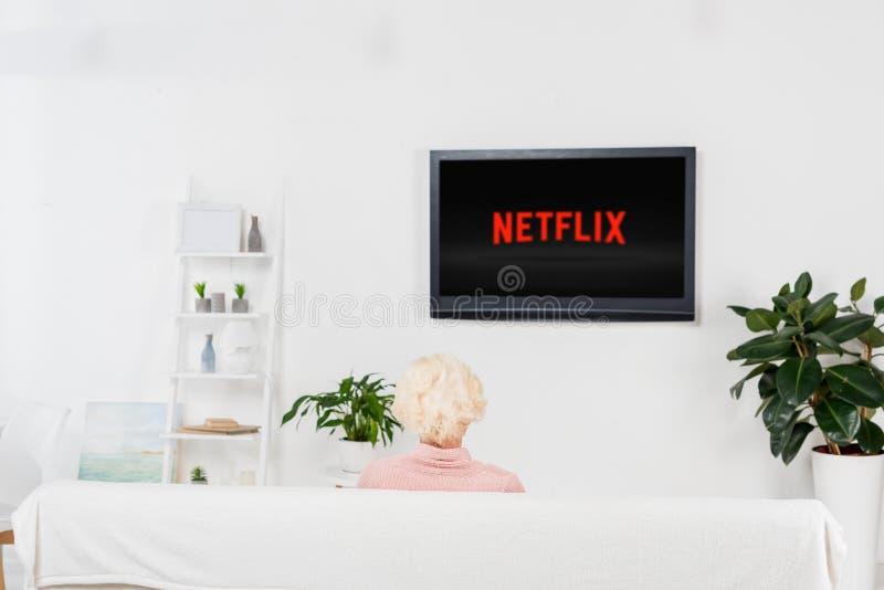 senior woman watching tv with netflix logo stock photo